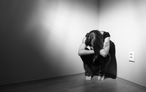 Young woman suffering from a severe depression (very harsh light